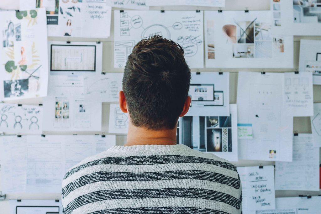 Man Wearing Black And White Stripe Shirt Looking At Wall