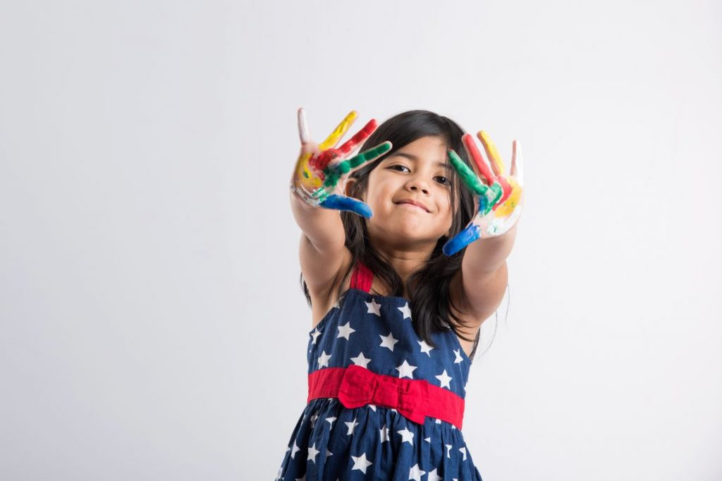 Indian little girl playing with colors